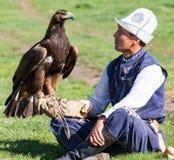 老鹰猎人拿着他的老鹰,坐地面 库存图片