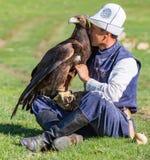 老鹰猎人拿着他的老鹰,坐地面 免版税库存照片