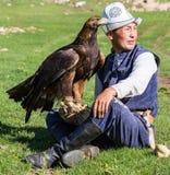 老鹰猎人拿着他的老鹰,坐地面 库存照片