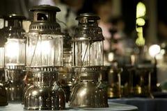 老黄铜灯用途煤油在桌在晚上,古老颜色图象上的组合点 r 免版税图库摄影