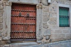 老黑褐色木门,两个敲门人,与磨碎的窗口和绿色色盲在托莱多,西班牙 免版税库存照片