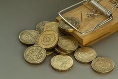老鼠陷井捉住一枚英磅硬币 库存图片