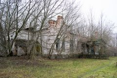 老,被忽略的,高傲的房子和门廊在树中 绿色老破裂的木头纹理被绘 免版税库存照片