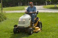 老年人在骑马割草机的切口草 免版税库存照片