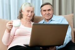 老年人 年长夫妇获得乐趣在沟通与在互联网上的家庭舒适的生活的 免版税库存照片