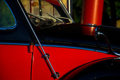 老经典甲虫红色和黑油漆工作侧视图  免版税库存图片
