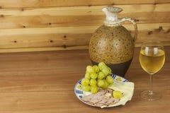 老黏土水罐和一杯在一张木桌上的酒 白葡萄酒和快餐 吃的火腿、乳酪和葡萄 免版税库存照片