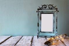 老维多利亚女王时代的钢青色空白框架的低调图象在日志树旁边的与在木桌上的神仙的圣诞灯 图库摄影