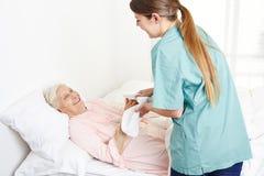 老年医学护士洗涤困于床 免版税库存图片