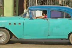 1955老绿松石驾驶通过哈瓦那,古巴街道的别克  免版税库存图片