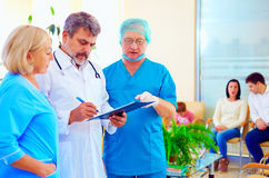 老练的咨询关于健康记录的医生和医护人员在医院 免版税库存照片