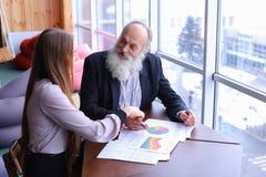老练的商人退休了微笑并且与ne分享忠告 免版税库存照片