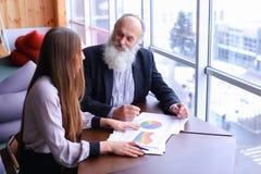 老练的商人退休了微笑并且与ne分享忠告 免版税图库摄影