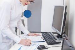 老练的女性研究员与纸一起使用 免版税库存照片