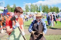 老练的铁匠教一个年轻人的工艺在节日 免版税图库摄影