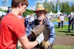 老练的铁匠教一个年轻人的工艺在节日 免版税库存照片