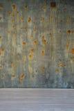 老绿色棕色表面和混凝土墙有生锈的斑点的在白色木地板上 免版税库存照片