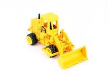 老黄色玩具拖拉机 库存图片