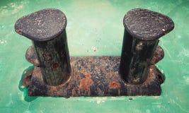 老黑色生锈了在绿色船甲板的系船柱 免版税库存图片