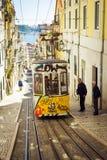老黄色缆索铁路在里斯本,葡萄牙狭窄的街道上  库存图片