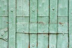 老绿色被绘的被铆牢的金属门细节 库存图片