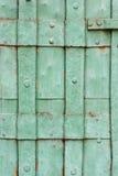 老绿色被绘的被铆牢的金属门细节 免版税库存图片