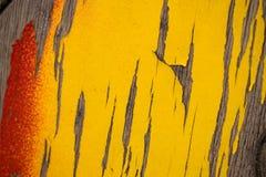 老破裂的油漆是平的木表面上的黄色红色 免版税库存照片