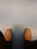 老黑裤子顶视图和黄褐色皮鞋放松在地板上的坐的商人 照片被聚焦在鞋子 Worki 库存图片