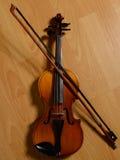 老说谎在木地板上的小提琴和打破的弓 库存图片