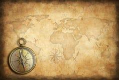 老黄铜或金黄指南针有世界地图背景 免版税库存图片