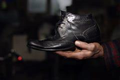 老黑鞋子在老人的手上 图库摄影