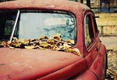 老MOBIL 在下落的叶子下的生锈的老汽车 免版税库存图片