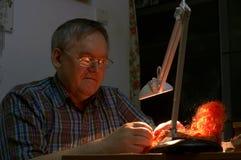 老Sartor在工作 裁缝修理桔子假发 免版税图库摄影