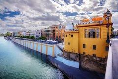 老Triana灯塔和瓜达尔基维尔河的河岸的五颜六色的房子在塞维利亚 库存图片