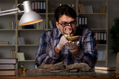 考古学家工作夜间在办公室 免版税库存图片