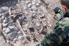 考古学挖掘 考古学家的手有开展对人的骨头的工具的研究,一部分的从gro的骨骼 免版税库存照片