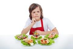 考虑下个创造性的三明治想法的年轻厨师 库存照片