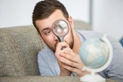 考虑与放大镜的人世界地球 图库摄影