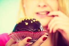 考虑吃的逗人喜爱的白肤金发的妇女杯形蛋糕 免版税图库摄影