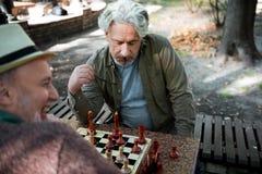考虑在棋枰的接下来的步骤的成熟男性领抚恤金者 图库摄影