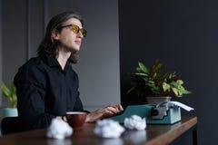 考虑新书的巧妙年轻作家,运作在一台老葡萄酒打字机,供以座位在一张桌上在办公室 免版税图库摄影