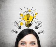 考虑新的企业想法小姐的头  一个电灯泡在混凝土墙上被画 免版税库存照片