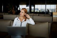 考虑新的想法的妇女为通过便携式计算机创造新的网站,当坐在现代舒适的内部时, 免版税图库摄影