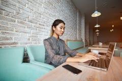考虑新的想法的年轻迷人的女性自由职业者在便携式计算机上的工作期间 免版税库存照片