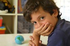 考虑旅行的男小学生世界 免版税库存照片