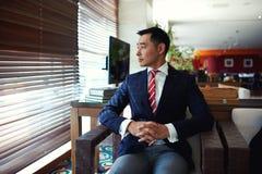 考虑某事的一个年轻成功的亚洲商人的画象,当坐在现代办公室内部空间时 图库摄影
