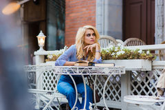 考虑某事的华美的白肤金发的夫人,当放松在新鲜空气时的咖啡店 库存图片