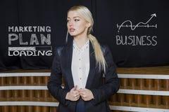 考虑赚钱的一名白肤金发的妇女的画象 到达天空的企业概念金黄回归键所有权 免版税库存照片