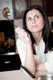 考虑食谱的少妇 免版税图库摄影