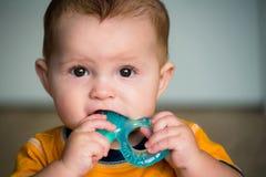 仔细考虑婴儿出牙时用的咬环的婴孩 库存照片